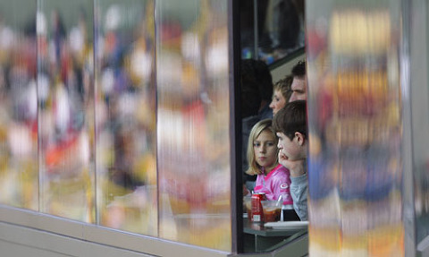 Reflection of the front of luxury boxes at Lambeau Field as fans watch the Packers game.