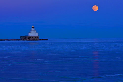 The moon rises over Lake Michigan and the Manitowoc, Wisconsin lighthouse.