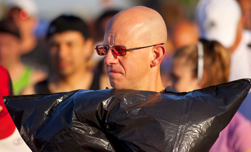 A runner keeps warm by wearing a black garbage bag before the race.