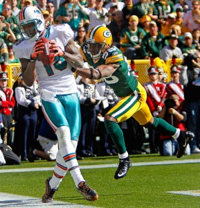 Miami Dolphins wide receiver Brandon Marshall can get both feet inbounds for a possible touchdown as Green Bay Packers cornerback Tramon Williams defends.