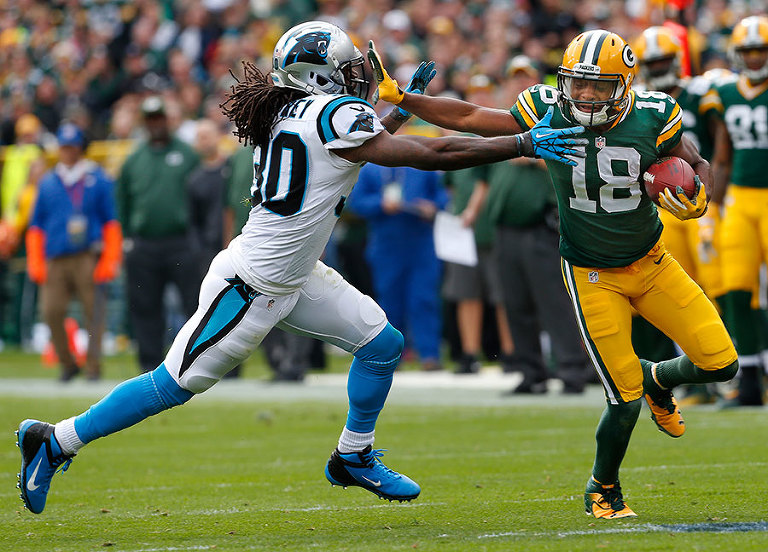Green Bay Packers wide receiver Randall Cobb stiff arms Carolina Panthers free safety Charles Godfrey on a first down catch.