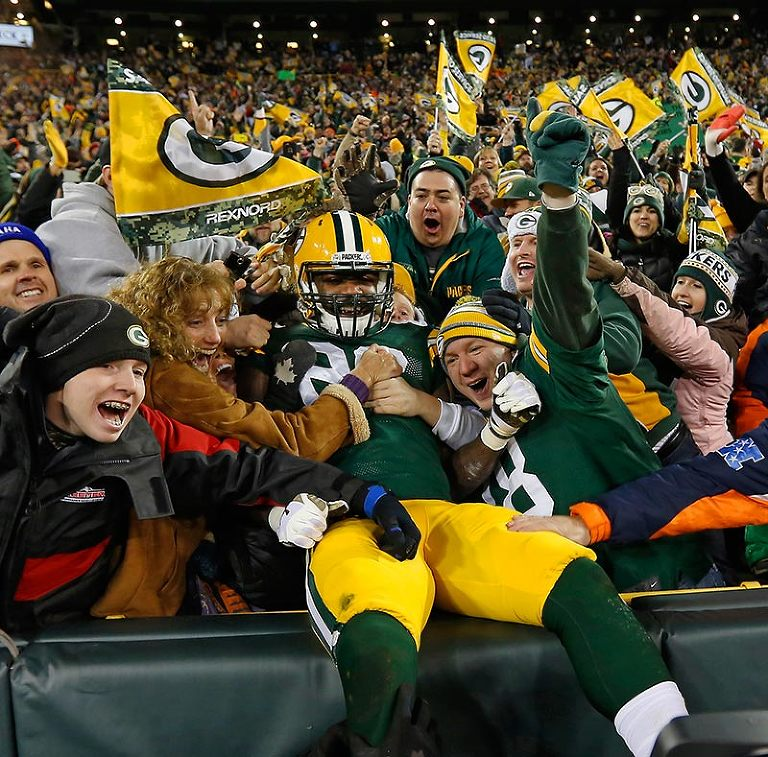 Green Bay Packers running back DuJuan Harris celebrates his touchdown with a Lambeau Leap.