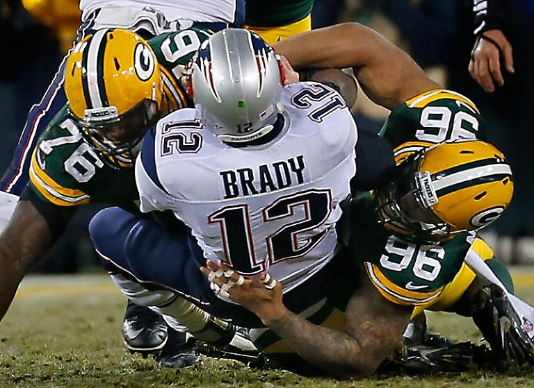 Green Bay Packers defensive end Mike Daniels and defensive end Mike Neal sack New England Patriots quarterback Tom Brady.