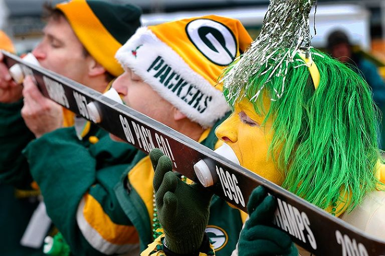 Packers fan get primed for the game by sharing a shotski while tailgating