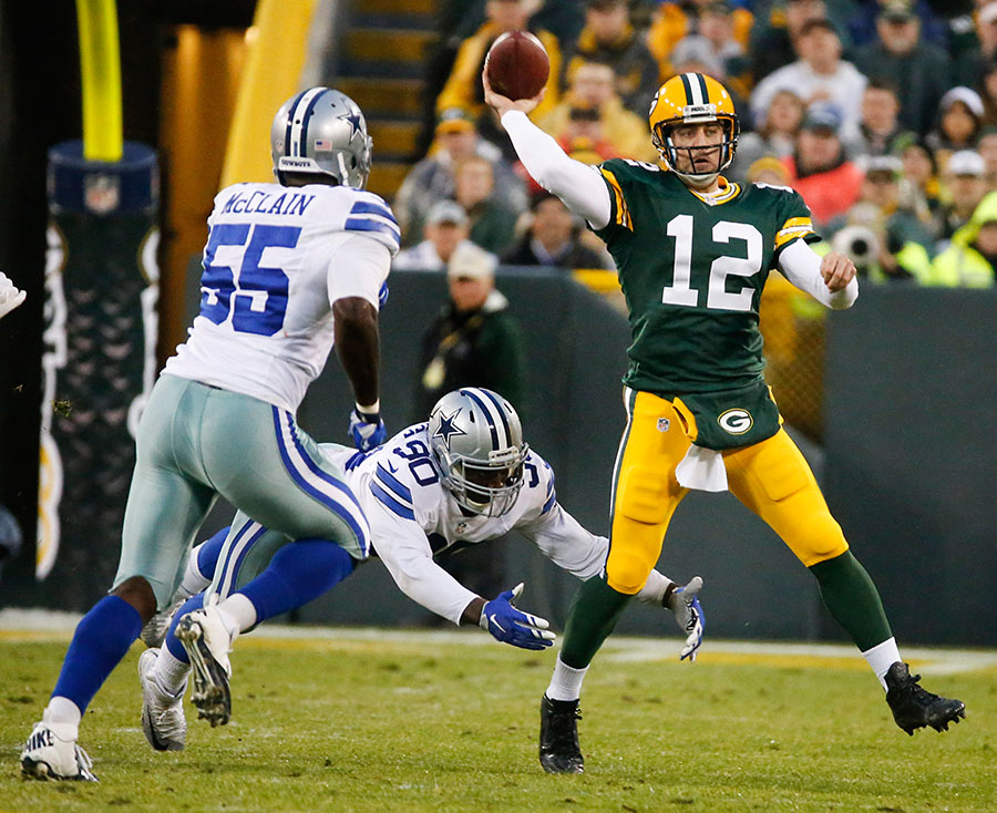 Green Bay Packers quarterback Aaron Rodgers eludes the pressure of Dallas Cowboys middle linebacker Rolando McClain and defensive end Demarcus Lawrence.
