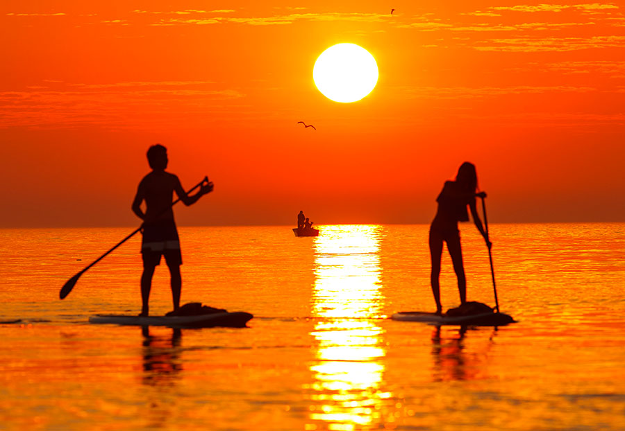 Sunrise stand up paddle boarding near the Manitowoc Lighthouse on Lake Michigan in Manitowoc, Wisconsin.