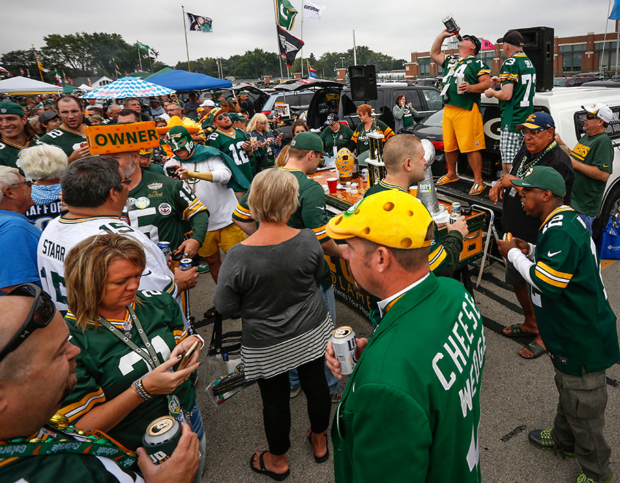 Green Bay Packers fans hydrate while tailgating.
