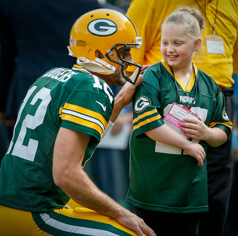 Green Bay Packers quarterback Aaron Rodgers poses for a photo with young fan before the game.