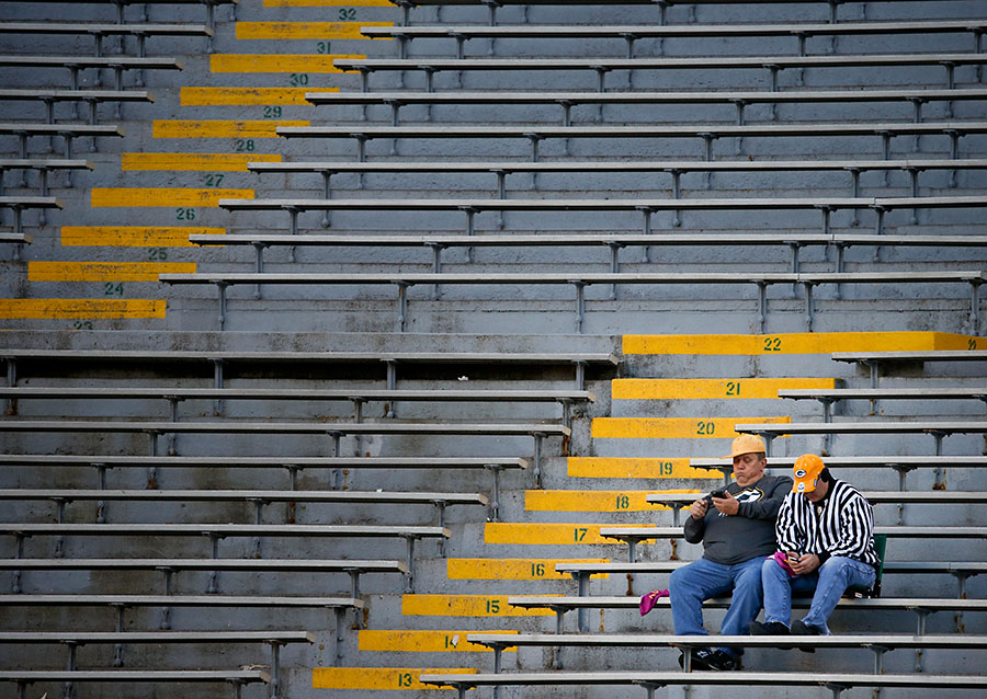 A couple early arrivals for the game try to figure out if they will be able to watch the presidential debate on their smart phone during the game.