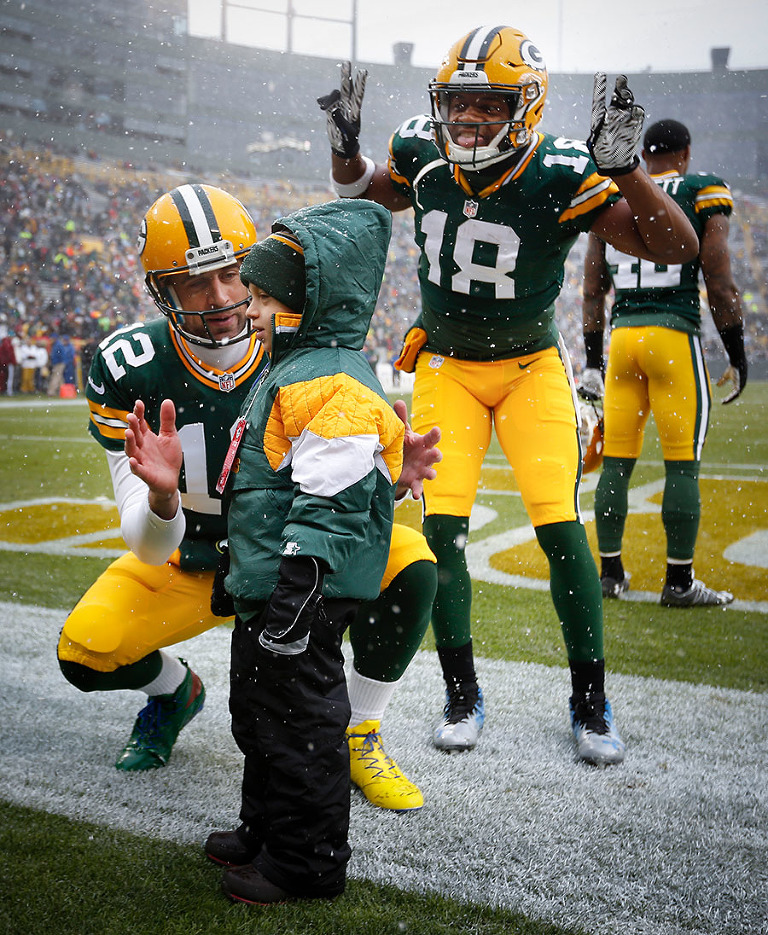 Green Bay Packers quarterback Aaron Rodgers and wide receiver Randall Cobb make a young fans day before the game.