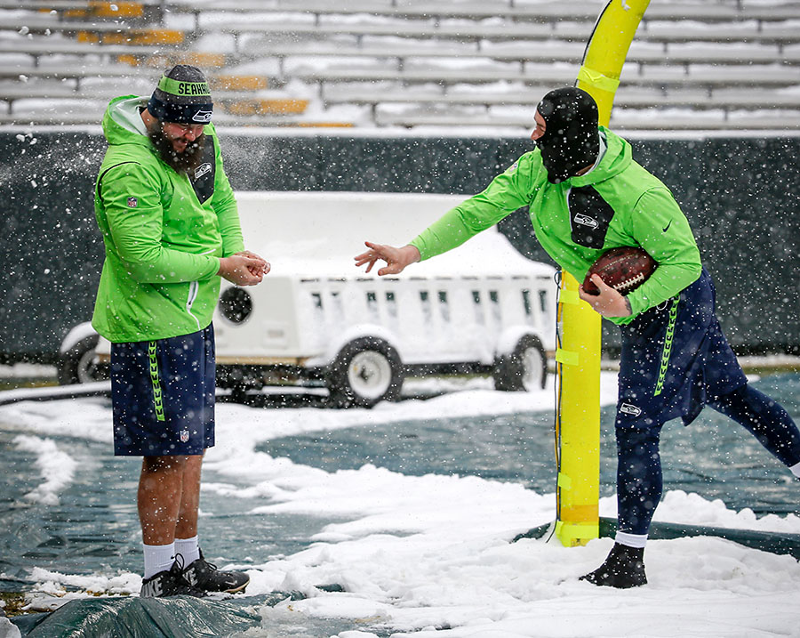 Seattle Seahawks' Justin Britt hits Mark Glowinski with a snowball as they head out on to the field to check the conditions before warmups.